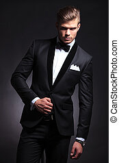 fashion man posing in tuxedo - elegant young fashion man...