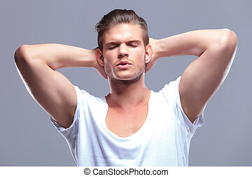 fashion man with eyes closed and hands behind head
