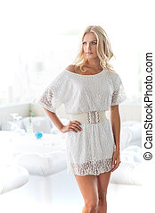 Fashion model. Attractive young blond hair woman in white dress holding her hand on hip and looking away
