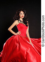 Fashion model. Beautiful woman wearing in magnificent red dress isolated on black background.