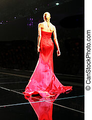 Blond model on the catwalk in a bright red sexy dress.