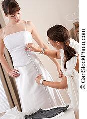 Fashion model fitting white wedding dress by designer - ...