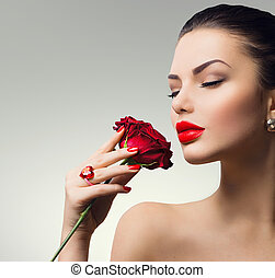 Fashion model girl portrait with red rose in her hand