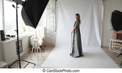 fashion model girl poses for the photographer in studio -...