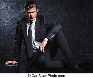 fashion model in black suit and tie is resting