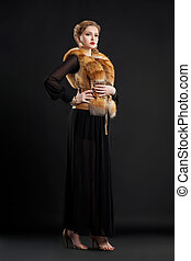 Fashion Model in Fur Collar and Black Dress Posing in Studio