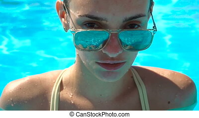 fashion model in mirror sunglasses looking at the camera in the pool