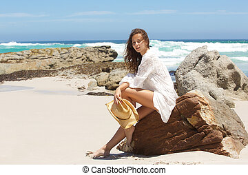 Fashion model in summer dress at the beach