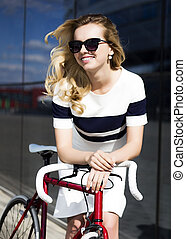 Fashion model in sunglasses poses near bicycle otdoors