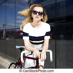 Fashion model in sunglasses poses near bicycle otdoors