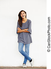 fashion model laughing against wall with arms crossed