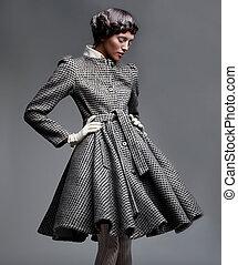 Fashion model lovely brunette in retro apparel posing in...
