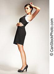 Fashion model Posed on light background in black dress
