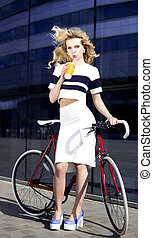 Fashion model poses near bicycle