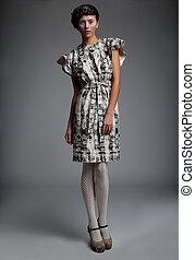 Fashion model pretty girl in retro dress standing in studio