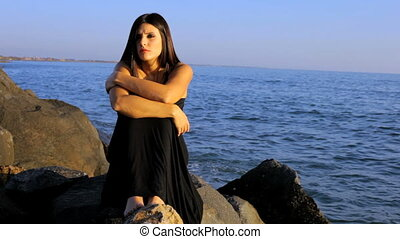 Fashion model sitting on rocks thoughtful in front of ocean