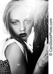 Fashion model with art makeup near tree