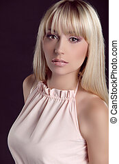 Fashion model with blond straight hair isolated on black background. Beauty photo