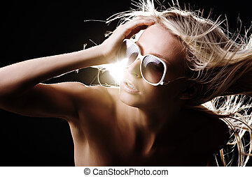 Fashion model with blonde hair blowing in studio