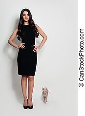 Fashion Model Woman in Black Dress with Cat on Background