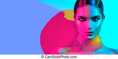 Fashion model woman in colorful bright lights posing. Portrait of beautiful sexy girl with trendy makeup