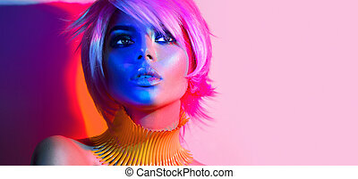 Fashion model woman in colorful bright lights posing. Portrait of beautiful sexy girl with trendy makeup and haircut