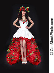 Fashion model woman wearing red roses dress isolated on black background