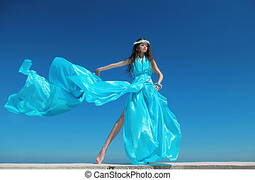 Fashion model woman with blowing dress over blue sky,...