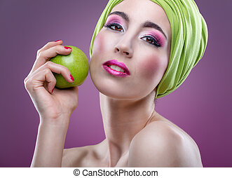 Fashion modell with beautiful pink makeup and green apple