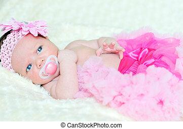 fashion newborn girl laying and wearing pink skirt