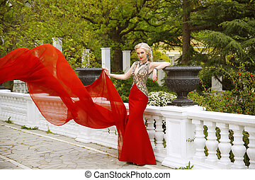 Fashion outdoor photo of beautiful sexy woman in gorgeous mermaid red dress with waving flying fabric. Elegant model posing on the balcony over green park.