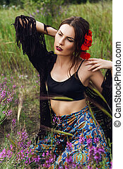 fashion outdoor portrait of a beautiful brunette woman with flowers in hair in the field