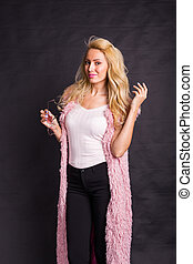 Fashion, people and beauty concept - Cute pretty blond woman posing on black background
