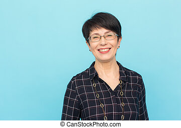 Fashion, people and style concept - Beautiful mid-aged woman wearing eye-glasses laughing on blue background with copy space
