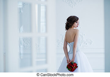 Fashion photo of a beautiful bride with flowers bouquet in her hands at the light room next to the doors