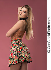 Fashion photo of a beautiful young woman in a pretty clothes with flowers posing on the pink background. Fashion photo
