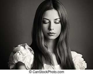Fashion photo of a young woman with dark hair. The...