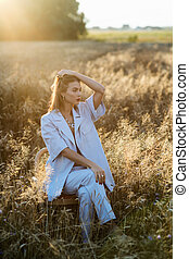Fashion photo of attractive blonde woman in blue suit in wheat field.