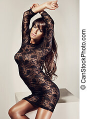 Fashion photo of beautiful brunette lady posing in black lace dress, sitting and keeping her hands up