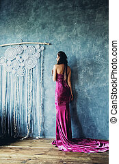 Fashion Photo of Beautiful Female Back in Gorgeous Dress on Blue Wall Background