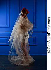 Fashion photo of beautiful girl under white veil and red flowers on her head on blue background