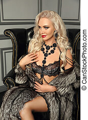 Fashion photo of beautiful stunning alluring woman in a sexy lingerie fur coat, posing in black armchair by wall with frame in luxury interior.