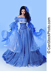 Fashion photo of beautiful woman in blowing magnificent dress. Studio photo