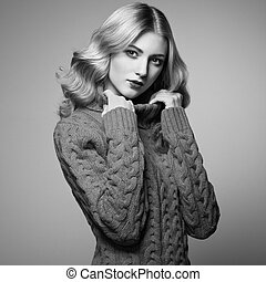 Fashion photo of beautiful woman in sweater. Curly...