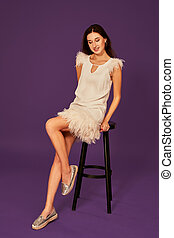 fashion photo of beautiful woman with brunette hair in white dress posing on chair at studio