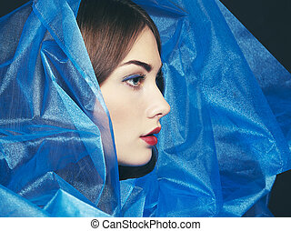 Fashion photo of beautiful women under blue veil. Beauty...