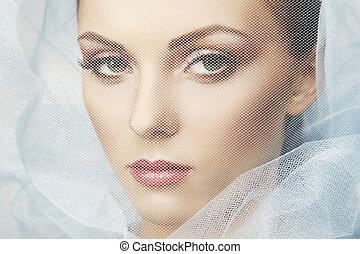 Fashion photo of beautiful women under blue veil. Beauty...