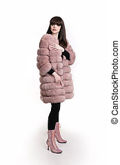 Fashion photo of fashionable woman in pink fur coat wears in trendy leather high boots posing isolated on studio background.