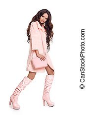 Fashion photo of fashionable woman in pink coat with handbag wears in trendy leather high boots posing isolated on studio white background.