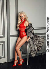 Fashion photo of Sexy alluring blond woman in red lingerie posing in fashion fur coat